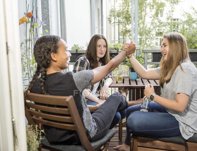 Three happy teenage girls sitting on a balcony — Stock Photo