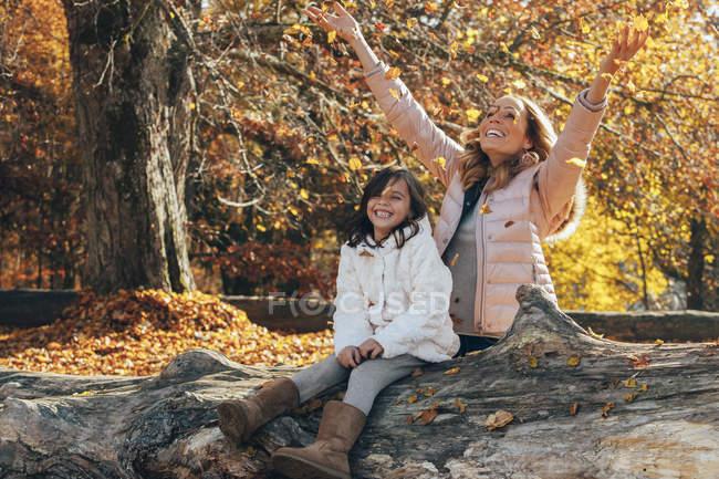 Madre y su hijita se divierten en el bosque otoñal - foto de stock