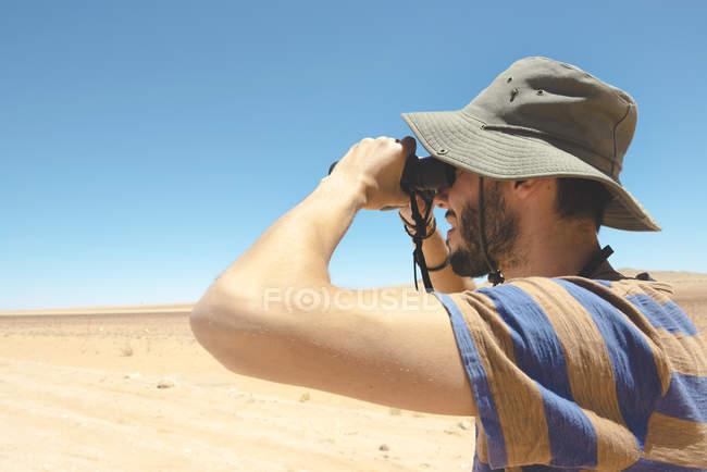 Намибия, пустыня Намиб, человек в шляпе, использующий бинокль, чтобы отвернуться — стоковое фото