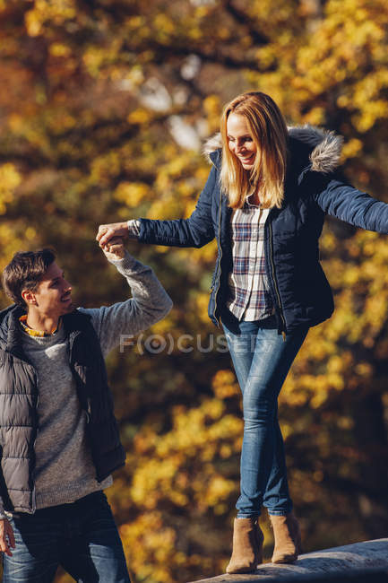 Man assisting woman balancing on trunk — Stock Photo