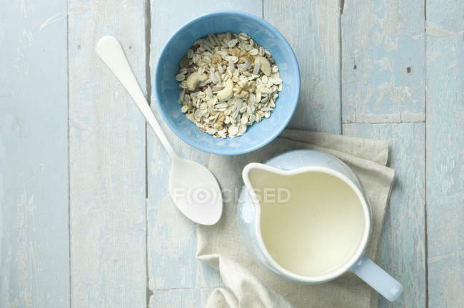 Bowl of granola with walnuts, cashew nuts, sunflower seeds and a milk jug — Stock Photo