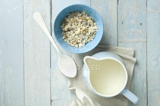 Чаша гранола з волоські горіхи, кеш'ю, насіння соняшнику і молока глечиком — стокове фото