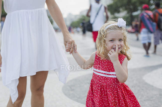 Grinning girl on mother's hand picking nose — Stock Photo