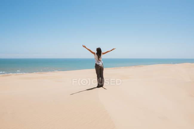 Namibia, Namib deserto, Swakopmund, donna nel deserto con il mare sullo sfondo — Foto stock
