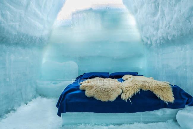 Habitación en hotel de hielo con cama contra la pared de hielo - foto de stock