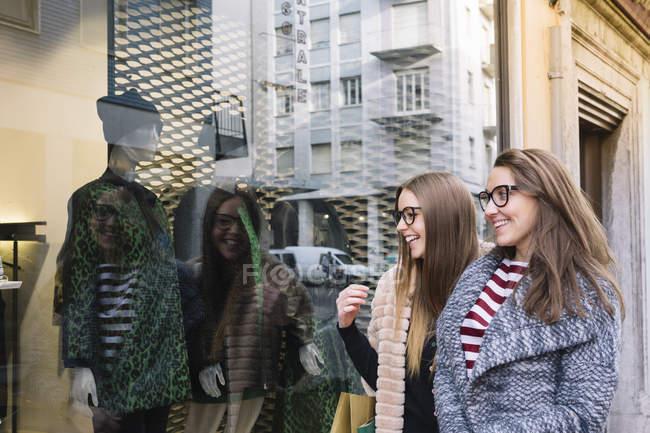 Italia, Belluno, due giovani donne che guardano la vetrina di un negozio di moda — Foto stock
