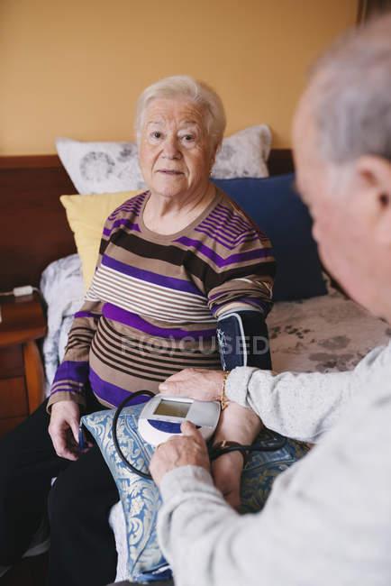 Homem sênior verificando a pressão arterial de sua esposa em casa — Fotografia de Stock