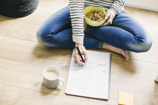 Woman sitting on floor with muesli bowl — Stock Photo