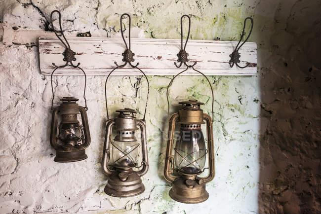 Antiguas lámparas de tormenta vintage en pared de piedra pintada - foto de stock