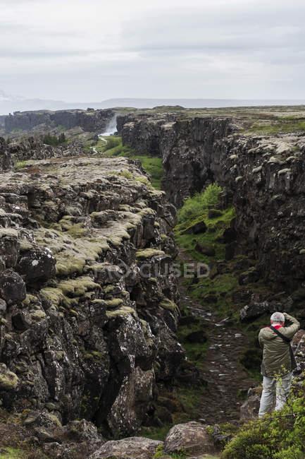 Исландия, зона разлома Тингвеллир и человек с камерой на скале — стоковое фото