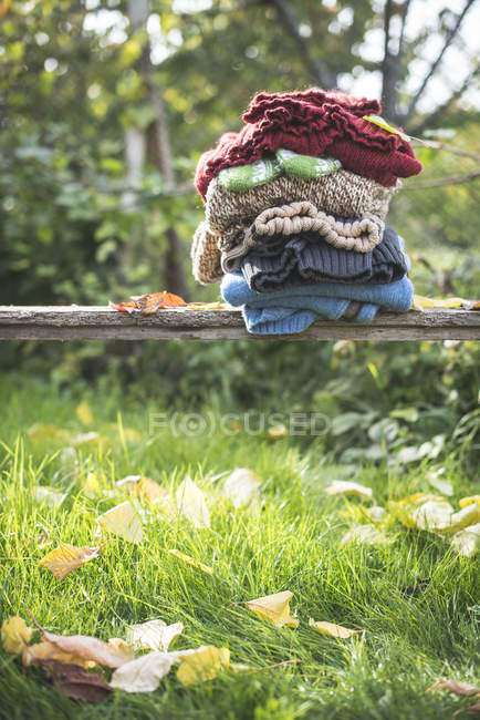 Stack of warm clothing in a garden — Stock Photo