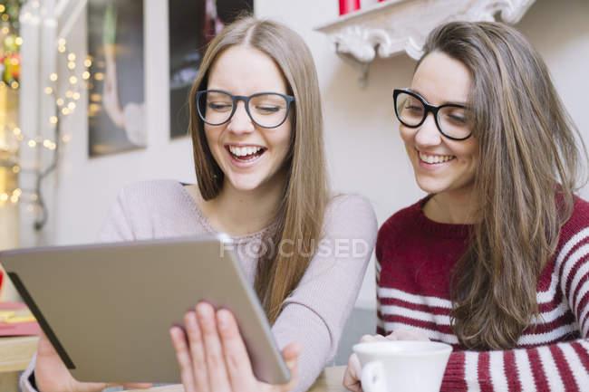 Deux jeunes femmes s'amusent avec une tablette numérique dans un café — Photo de stock