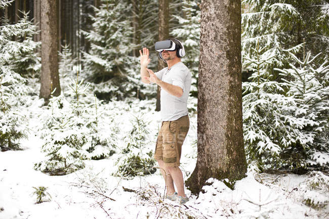 Man wearing Virtual Reality Glasses in winter landscape — Stock Photo