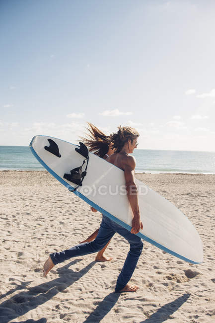 Coppie che funzionano con i surf alla spiaggia — Foto stock
