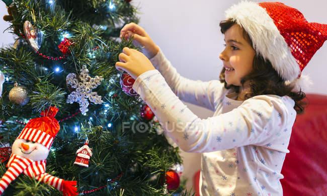 Feliz niña con gorro de Navidad decoración árbol de Navidad - foto de stock