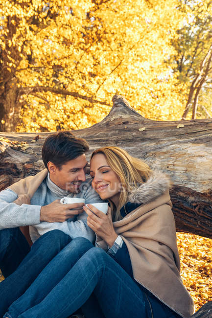 Couple holding cups in autumn forest — Stock Photo