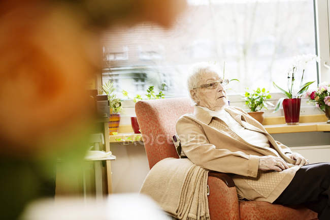 Portrait of senior woman with Alzheimer's disease sitting in her room at retirement home — Stock Photo