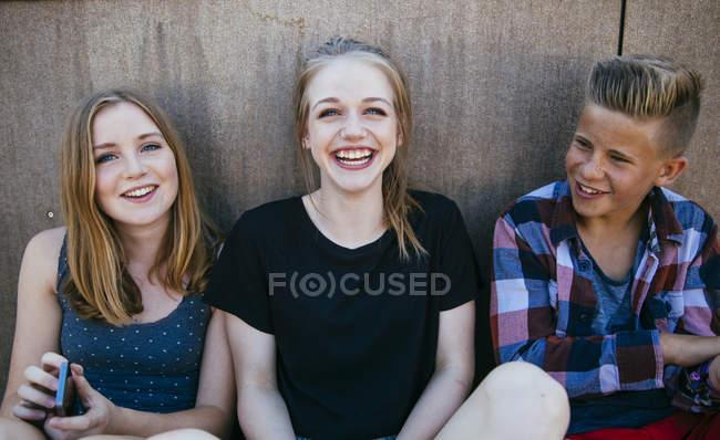 Three happy teenagers sitting outdoors — Stock Photo