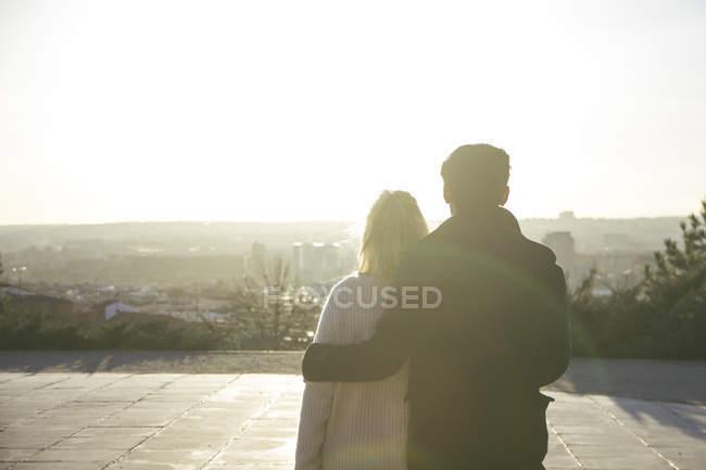 Испания, Мадрид, вид сзади влюбленной молодой пары при подсветке — стоковое фото