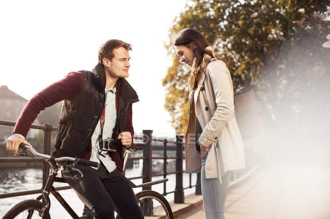 Germania, Berlino, giovane coppia al fiume Sprea in bicicletta — Foto stock