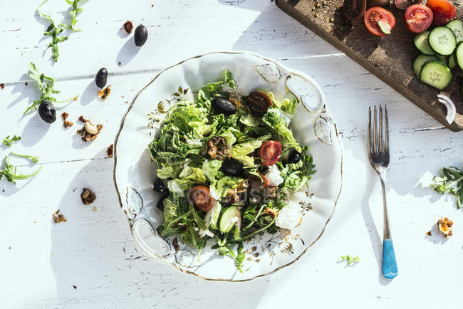 Greek salad with arugula, cheece, olives, tomatoes, cucumber, onion and caramelized nuts — Stock Photo