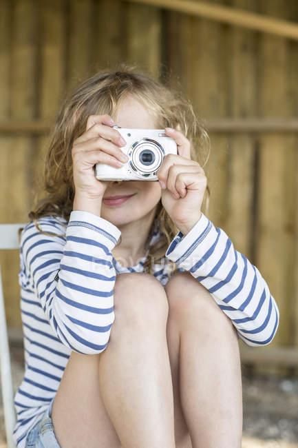 Sorrindo menina loira tirando uma foto com uma câmera digital — Fotografia de Stock