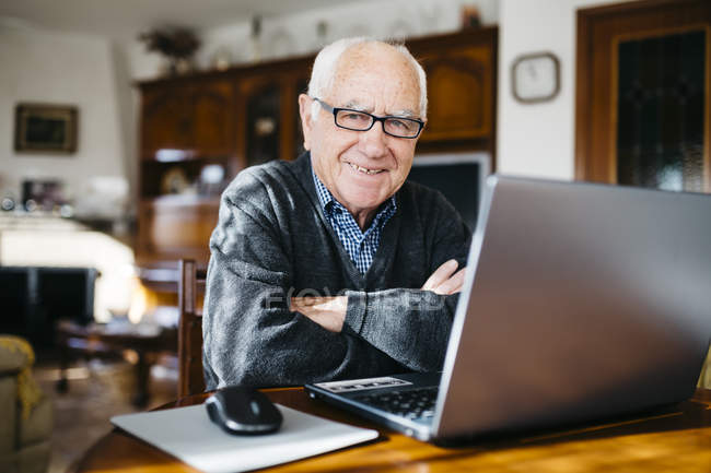 Senior man sitting with laptop at home — Stock Photo