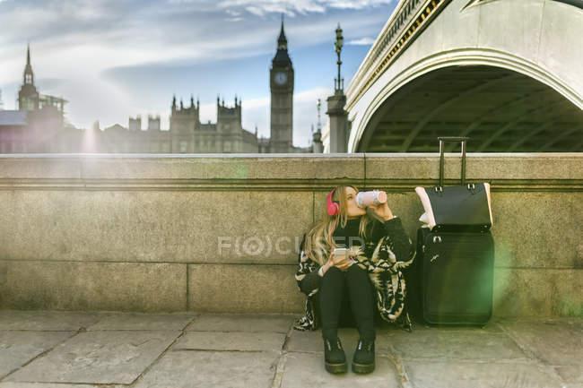 Reino Unido, Londres, jovem mulher ouvindo música perto de Westminster Bridge — Fotografia de Stock
