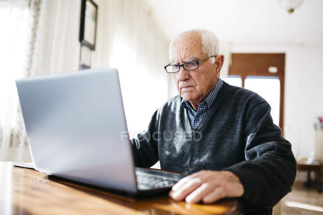 Senior man using laptop — Stock Photo