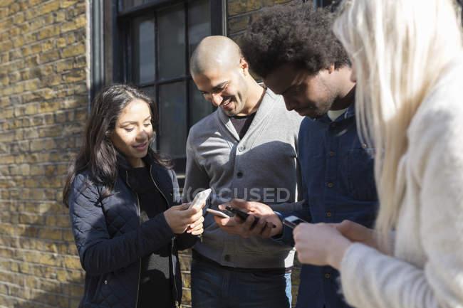 Amigos felizes usando telefones celulares, em frente ao prédio de tijolos — Fotografia de Stock