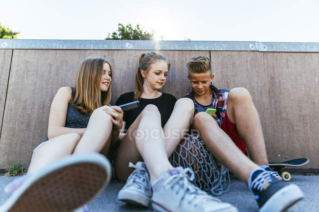 Three teenagers sitting outdoors with smartphones — Stock Photo