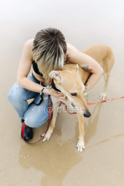Spain, Llanes, young woman with her greyhound on the beach — Stock Photo