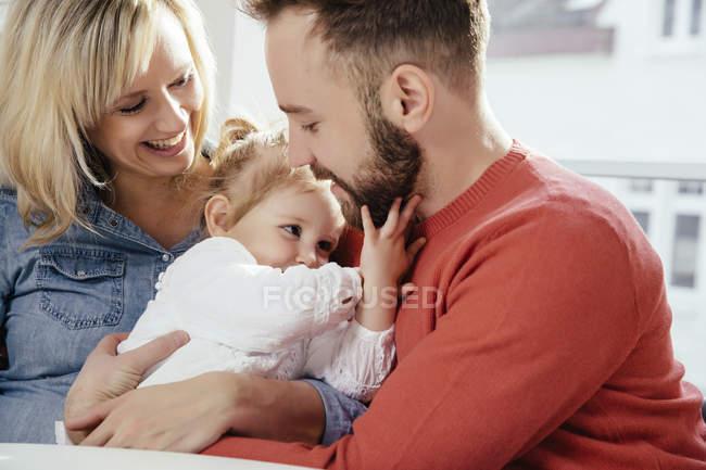 Pais abraçando sua filhinha — Fotografia de Stock