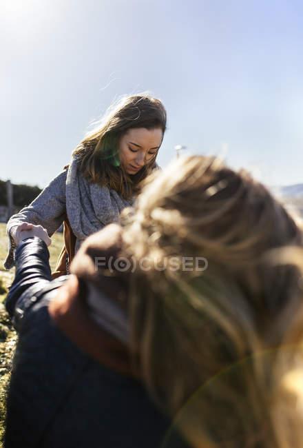 Junge Frau, die Hand auszustrecken, für ihren Freund — Stockfoto