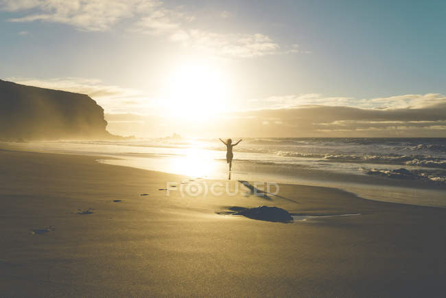 Woman at the beach running to the water at sunset — Stock Photo