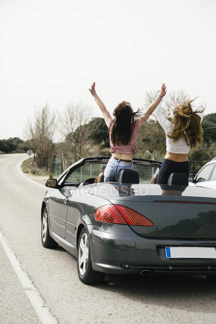 Women having fun in a convertible car on a country road — Stock Photo
