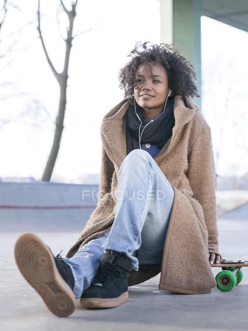 Улыбающаяся молодая женщина, сидящая на длинном борту и слушающая музыку с наушниками — стоковое фото