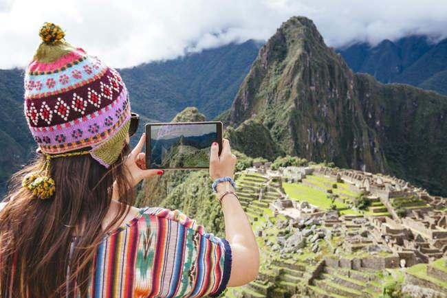 Peru, mulher tirando fotos da Cidadela de Machu Picchu e Huayna Picchu montanha com um tablet — Fotografia de Stock