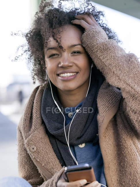 Portrait of smiling young woman  hearing music with earphones — Stock Photo
