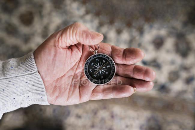Mano dell'uomo maggiore che tiene la bussola, primo piano — Foto stock