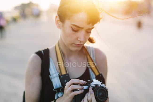 Молодая женщина смотрит на камеру на закате — стоковое фото