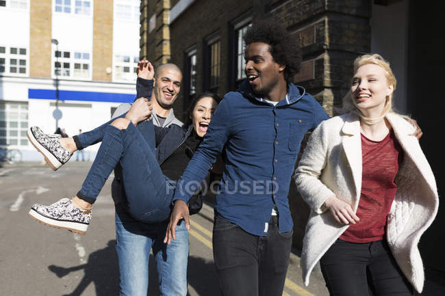 Laughing friends having fun on urban street — Stock Photo