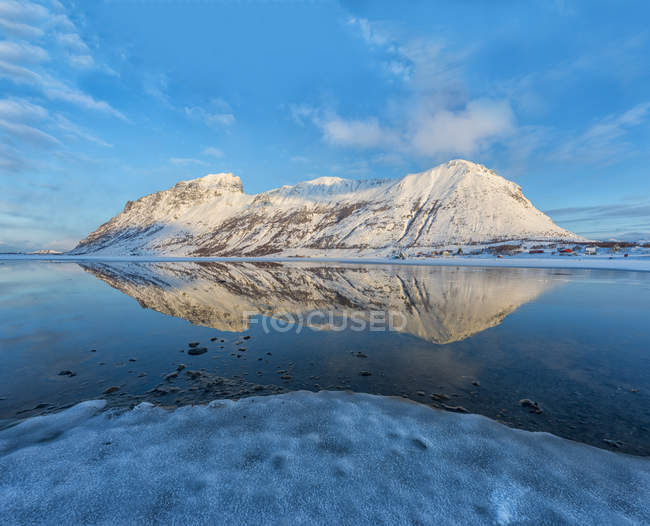 Norway, Mountain reflected in a frozen lake at sunset — Stock Photo