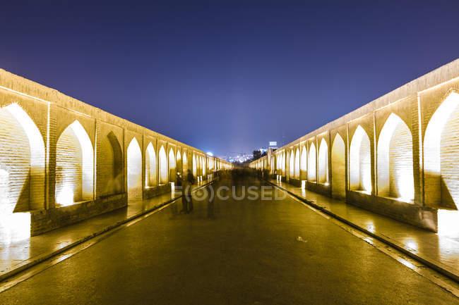 Irán, Isfahán, iluminado puente de arco Siosepol por la noche - foto de stock