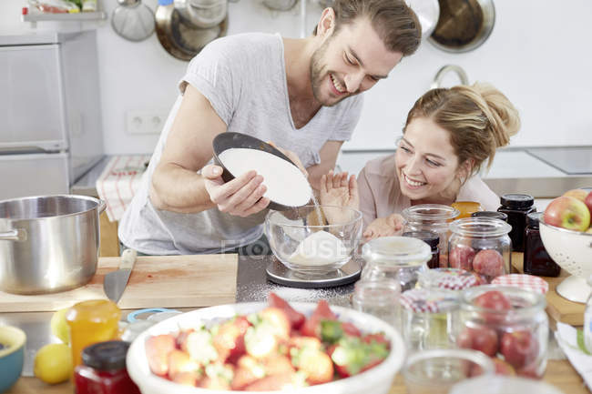 Couple dans la cuisine verser le sucre dans un bol — Photo de stock