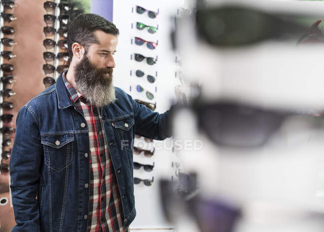 Man choosing glasses in optical store — Stock Photo