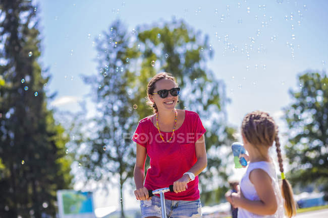 Щаслива мама з донькою робить мильних бульбашок — стокове фото