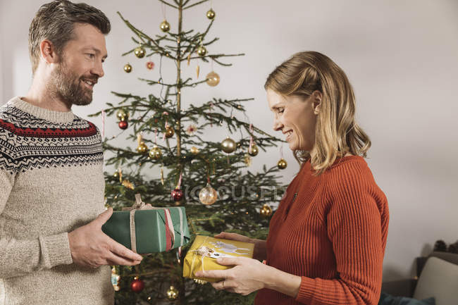 Regali Di Natale Per Coppia.Coppie Che Scambiano I Regali Di Natale Davanti All Albero Di Natale