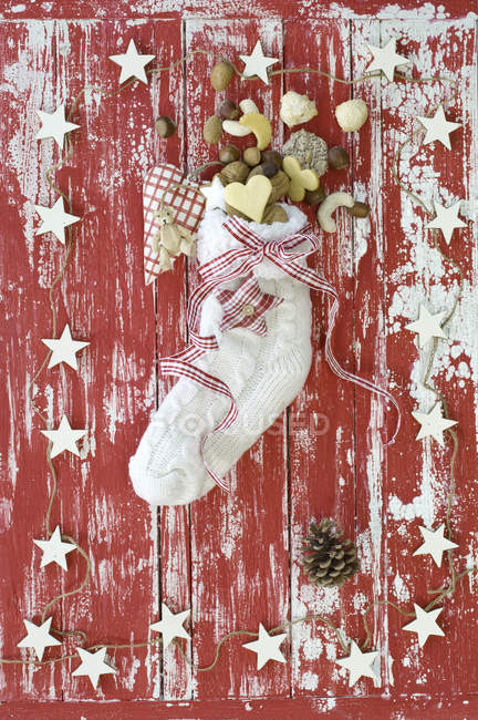 Sock filled with Christmas cookies on red wooden surface — Stock Photo