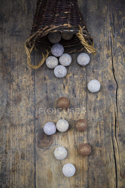 Different sorts of truffles and a wickerbasket on wood — Stock Photo